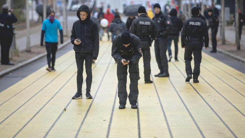 ضابط شرطة يلتقط صورة تذكارية للوحة صفراء كتبت عليها أسماء المدن والبلدات الألمانية التي رسمت بمناسبة الاحتفال بيوم وحدة ألمانيا. إي.بي.إيه