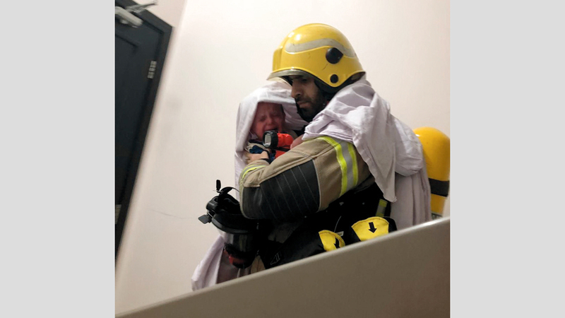 رجل إطفاء ينقذ طفلاً من الدخان. من المصدر