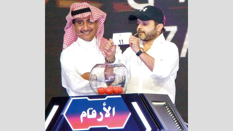 من مراسم إجراء القرعة بحضور الفنانين المصري والسعودي محمد هنيدي وناصر القصبي. من المصدر