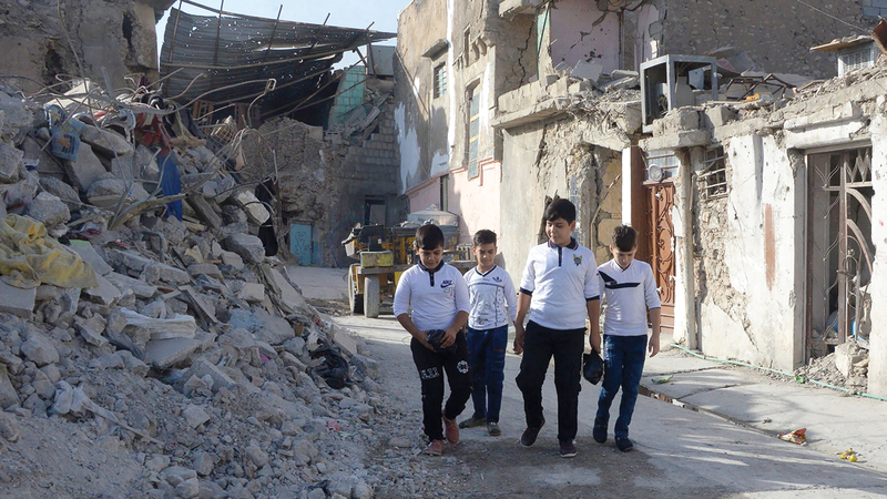 أطفال عراقيون في طريقهم إلى المدرسة وسط مباني الموصل المهدمة بعد تحريرها من «داعش». أ.ف.ب