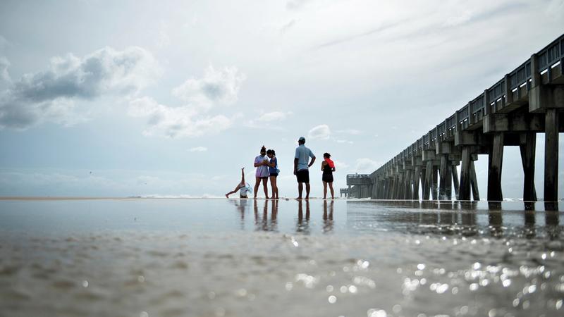 مواطنون أميركيون يقفون على شاطئ خليج المكسيك مع اقتراب الإعصار «مايكل».  أ.ف.ب