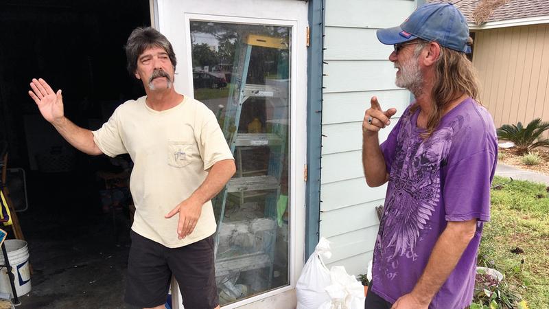 شخصان يناقشان ما إذا كان يتوجب ترك البيت بسبب الإعصار في أحد أحياء بنما سيتي بولاية فلوريدا. أ.ب
