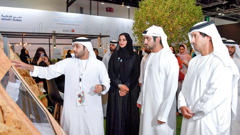 مكتوم بن محمد يتابع شرحاً عن الابتكارات المعروضة في أجنحة حكومة دبي.  من المصدر