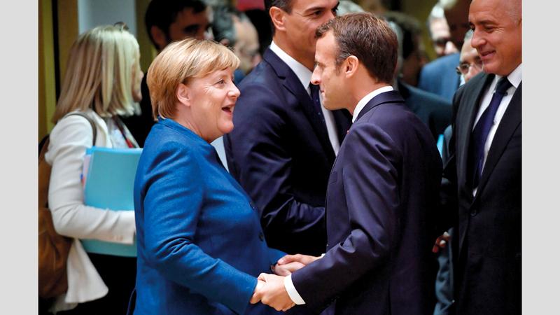 ميركل والرئيس الفرنسي خلال القمّة.  أ.ف.ب