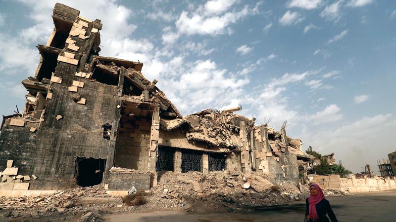 سورية تمرّ أمام مبنى مدمّر في الرقة. أ.ف.ب
