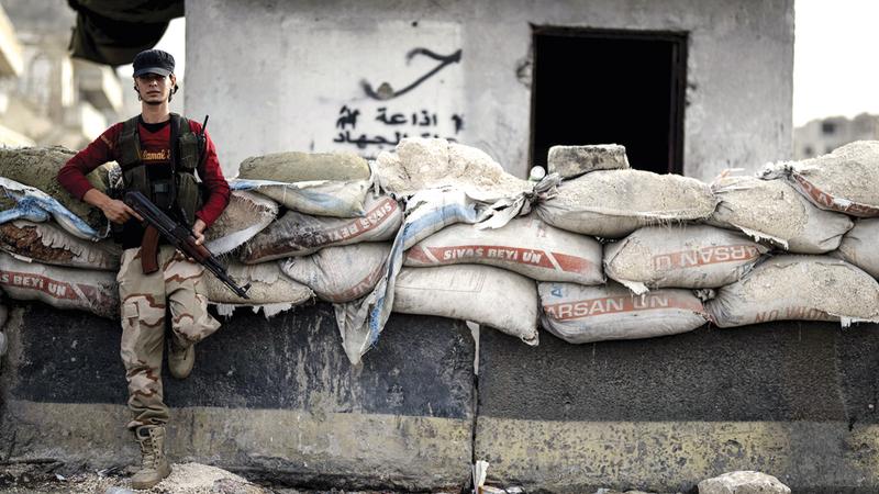 مقاتل من المعارضة السورية في إحدى نقاط التفتيش بإدلب. أ.ب