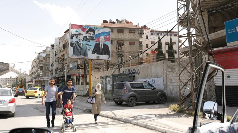 صور بوتين والأسد ونصرالله تنتشر في شوارع دمشق. إي.بي.إيه
