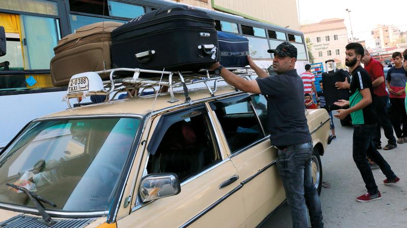 مسافرون يحملون حقائبهم قبيل انطلاق الرحلة التي لا يعرفون ان كانت ستتم ام لا.  ا.ف.ب