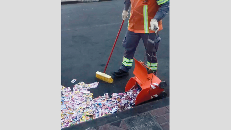 عمال بلدية دبي ينظفون الأرض من آلاف البطاقات.  الإمارات اليوم