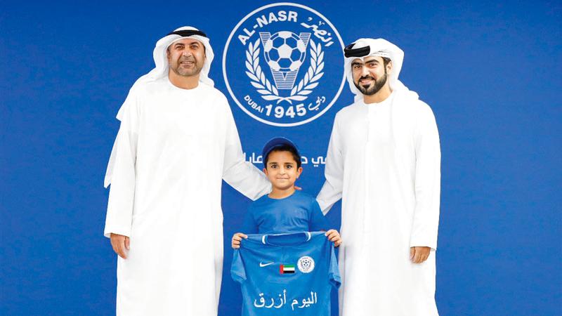 عبدالرحمن أبوالشوارب وحمد الفلاسي يكرّمان المشجع الصغير. من المصدر