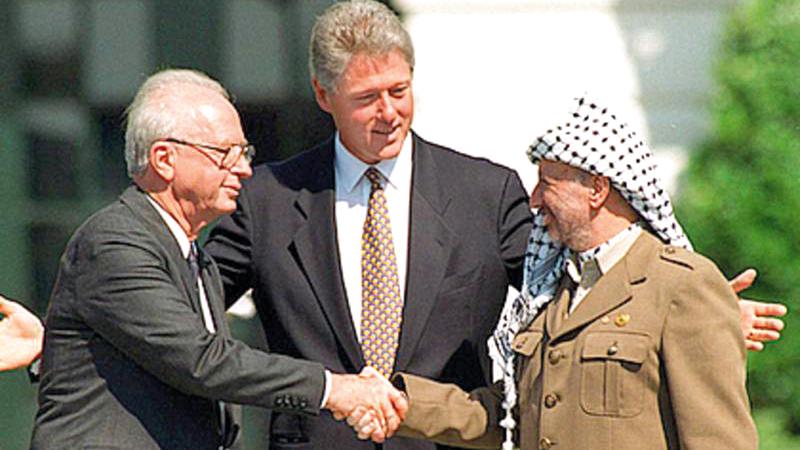 عرفات يصافح رئيس الوزراء الإسرائيلي السابق إسحاق رابين بحضور كلينتون خلال توقيع اتفاقية أوسلو.  غيتي