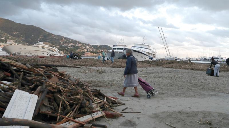امرأة إيطالية تمر قبالة حطام القوارب. أ.ب