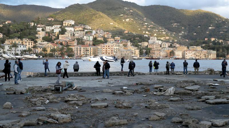 مواطنون إيطاليون يعاينون القوارب التي قذفتها أمواج البحر بسبب ارتفاع منسوب المياه بعد موجة باردة تخللتها أمطار غزيرة. أ.ب