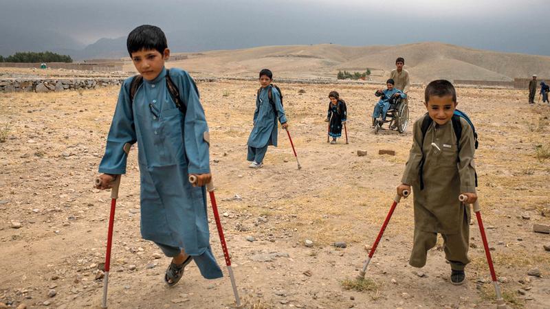 (من اليسار إلى اليمين) «بشير، منجل، مروة، عبدالرشيد (على كرسي متحرك)، أمان، وعلى مسافة (ربيع)» خلال ذهابهم إلى المدرسة.  من المصدر