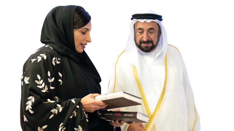سلطان القاسمي يطّلع على أحد الإصدارات بحضور بدور القاسمي.  الإمارات اليوم