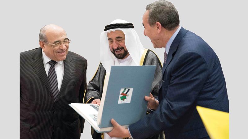 سلطان القاسمي يطلع على أحد الكتب بحضور عزالدين ميهوبي ومحمد صابر عرب. من المصدر