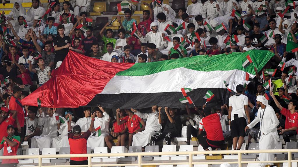 الجماهير خلال مباراة الوحدة وضيفه شباب الأهلي، أمس، ترفع العلم الوطني عالياً. ويُذكر أن اللقاء كان ضمن الجولة الثامنة من دوري الخليج العربي وانتهى بتعادل الفريقين 2-2. تصوير: إريك أرازاس
