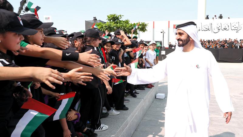 نائب رئيس الدولة مصافحاً طلبة مدارس دبي الحكومية والخاصة المشاركين في الاحتفالية. وام