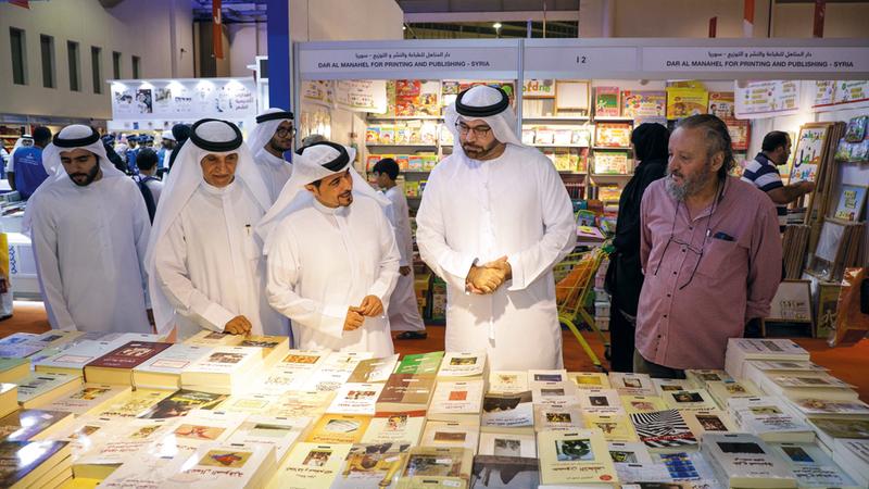 محمد القرقاوي خلال جولته في أروقة المعرض بحضور أحمد العامري وعدد من الشخصيات الثقافية. من المصدر