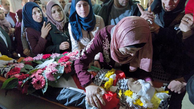 أسرة الشهيد الفلسطيني محمد شريتح تلقي النظرة الأخيرة على جثمانه. أسوشيتد برس