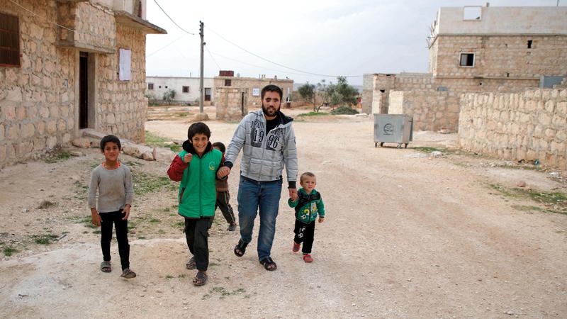 أحمد يمسك بطفله وهو يلعب مع عدد من أطفال الحي.  أ.ف.ب