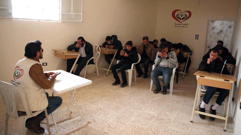 «أحمد» يقدم درساً لطلابه المكفوفين. أ.ف.ب
