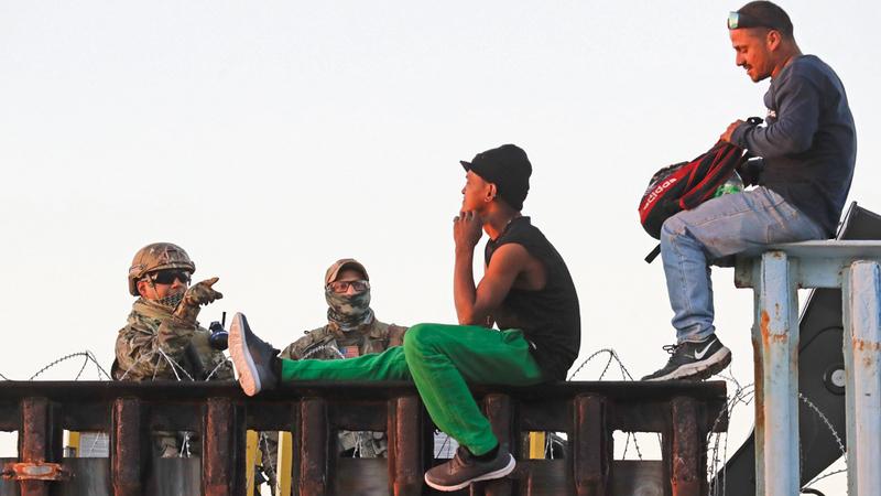 مهاجرون يجلسون على بعض المنشآت في الحدود الفاصلة بين الولايات المتحدة والمكسيك.  أ.ب
