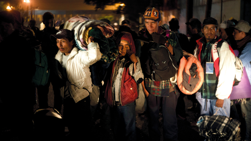 مهاجرون يستعدون للدخول إلى مأوى ملاصق لجدار الحدود.  أ.ب