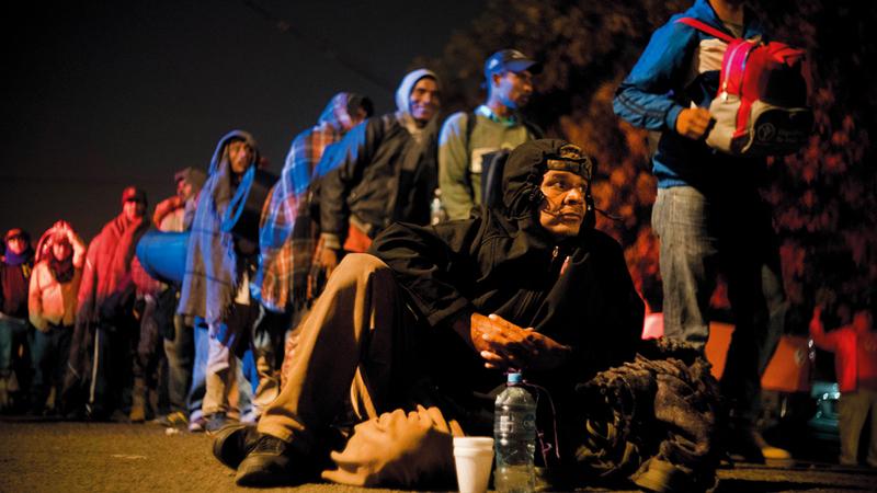 مهاجرون يستريحون على الأرض بعد الشعور بالإرهاق جراء السير لمسافات طويلة.  أ.ب