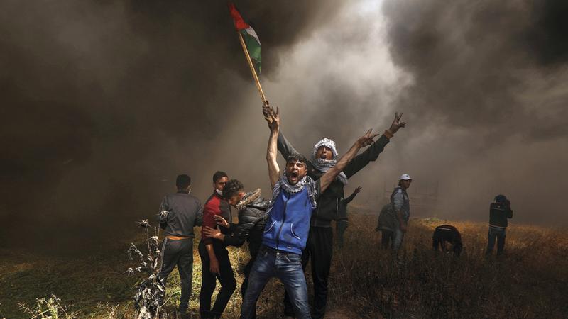 متظاهرون فلسطينيون خلال مواجهات مع جنود الاحتلال على الحدود مع قطاع غزة. رويترز