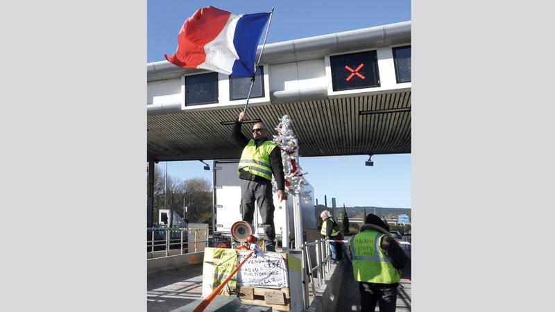 أحد محتجي «السترات الصفراء» يرفع العلم الفرنسي. أ.ب