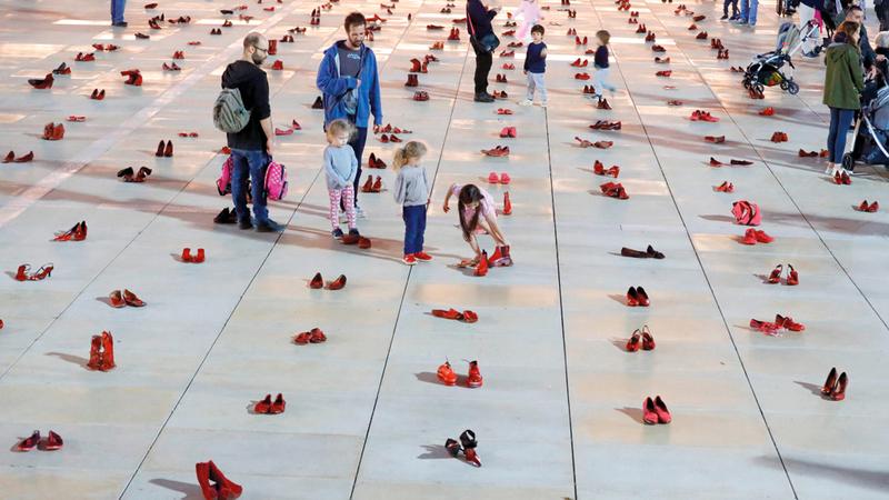 المتظاهرات فرشن أرض ساحة رابين في تل أبيب بالأحذية الحمراء تعبيراً عن احتجاجهن. أ.ف.ب