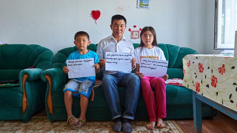 «إسلام» وابنته وابنه يرفعون لافتات تطالب بإطلاق سراح أمهم خلال اعتقالها في كازاخستان.  غيتي