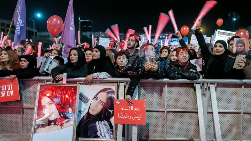 النساء يحملن صوراً لنساء قُتلن ضمن أحداث عنف أسري.  إي.بي.إيه