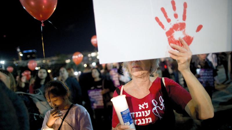 سيدة تحمل لافتة احتجاجية بلون الدم احتجاجاً على العنف  ضد النساء.  أ.ب
