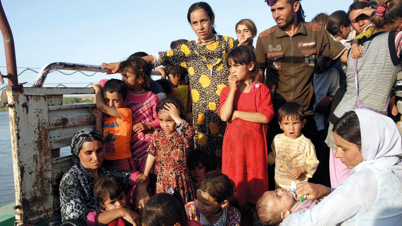 عائلات إيزيدية تفرّ من العنف الذي طالها في سنجار خوفاً من «داعش». رويترز