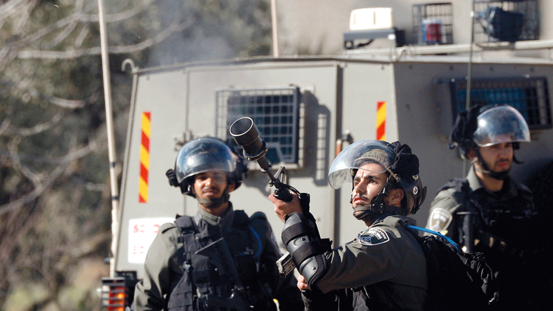 شرطي إسرائيلي يطلق قنابل الغاز على الفلسطينيين في رام الله أمس. رويترز
