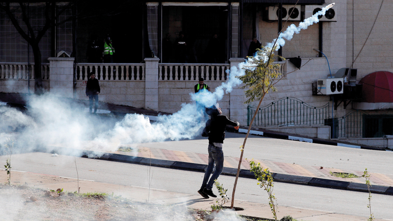 شاب فلسطيني في رام الله يتصدى لقنبلة غاز ويلقيها بعيداً. رويترز