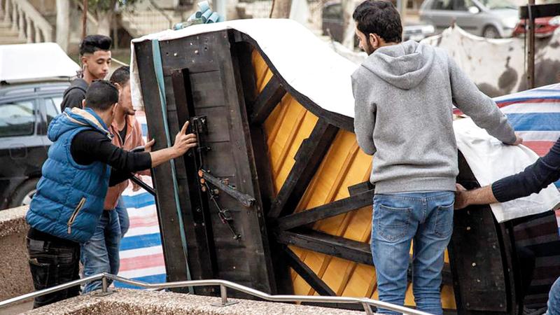طلاب في المعهد يحملون البيانو الضخم الذي أعادت النرويج تأهيله بعد إعطابه بسبب ظروف الحرب والحصار. من المصدر