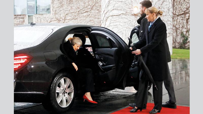 ماي لم تستطع الخروج من السيارة لدى لقاء ميركل بسبب انغلاق الباب. غيتي