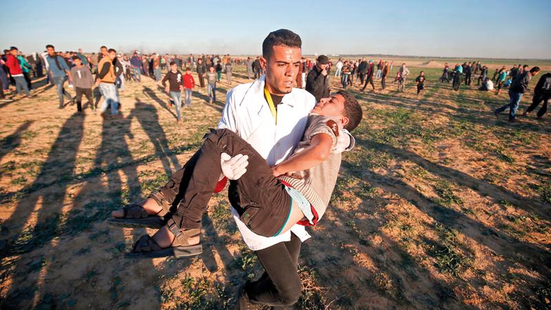 إجلاء فلسطيني أصيب بالمواجهات مع الاحتلال في غزة. رويترز