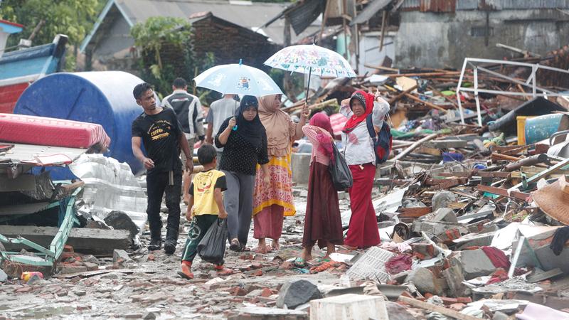 سكان محليون في إندونيسيا يسيرون بين الأنقاض. إي.بي.إيه
