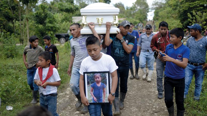 طفل يحمل صورة للطفلة المتوفاة وهو يتقدم موكب جنازتها.  أ.ف.ب