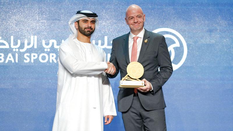منصور بن محمد خلال تكريمه رئيس «فيفا» إنفانتينو  في مؤتمر دبي الرياضي. الإمارات اليوم
