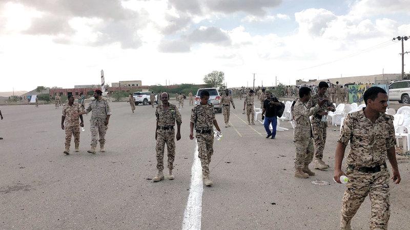 جنود يمنيون يتفحصون موقع عدوان الحوثي على قاعدة العند بطائرة مسيرة. رويترز