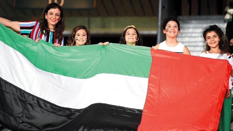 مشجعات المنتخب الوطني يرفعن علم الدولة على المدرّجات. تصوير: إريك أرازاس