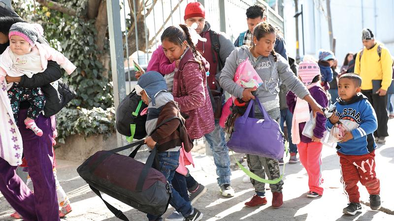 مجموعة من المهاجرين من هندوراس والمكسيك وكوبا وغواتيمالا ينتظرون  اجتياز الحدود إلى داخل الولايات المتحدة.  أ.ف.ب