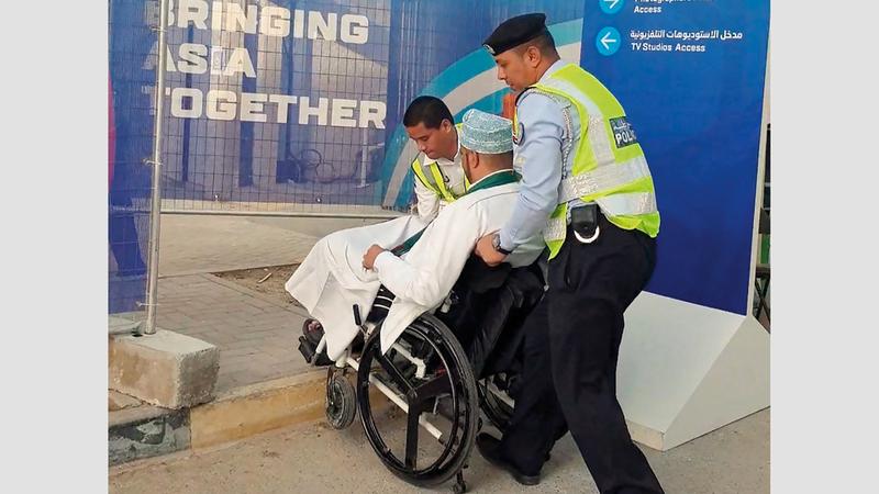 أحد أفراد الشرطة والمتطوعين يساعدان أحد المشجعين على دخول استاد الشارقة.  تصوير: أسامة أبوغانم