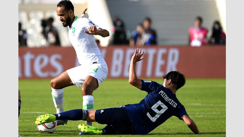 عبدالله عطيف (يسار) يتجاوز اللاعب الياباني مينامينو. تصوير: باتريك كاستيلو