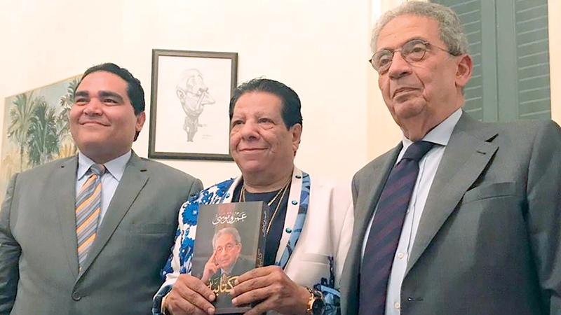 عمرو موسى يهدي نسخة من كتابه للمغني شعبان عبدالرحيم.  أرشيفية